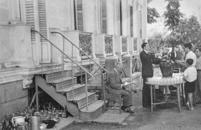 [Vista de un hombre sirviendo bebida en los jardines de la Embajada Alemana de Madrid a las personas refugiadas tras el estallido de la Guerra Civil. Hombres sentado leyendo el periódico junto a él]