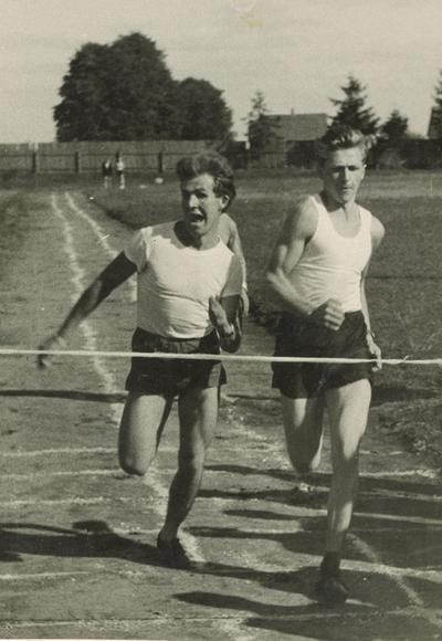 """Nuotrauka """"Vytautas Bikneris (dešinėje) 1500 m. bėgimo rungtyje prie finišo linijos varžymų metu 1963 m. buvusiame Tauragės miesto stadione"""""""