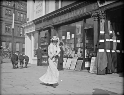 Woman walking past stationery shop, O'Connell Street. View of shop fronts, including No. 35 Catal  Broin (Charles Byrne), stationer and newsagent, and No. 36, John Averill, confectioner. Woman, wearing hat, walking in foreground and group of children playing in background.