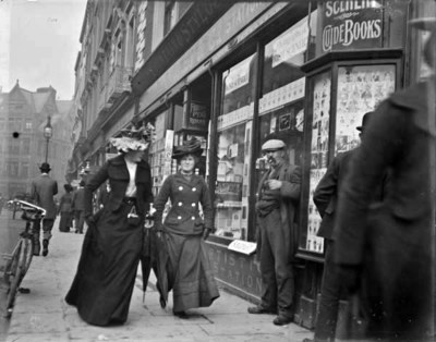 Two women, one wearing necktie, walking on Grafton Street. Two women are both wearing hats, woman on the left is holding a muff in her right hand, women on the right is wearing a tie. Bystanders and shop-fronts visible in the background