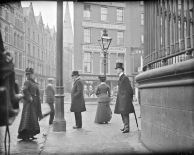 Man with umbrella standing at the junction of Nassau Street, Grafton Street and Suffolk Street. View from Nassau Street at the corner of Trinity College. Hamilton, Long and Co., Apothecaries, No. 107 Grafton Street in background