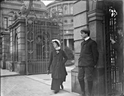 Woman wearing orthopaedic shoe, walking through the gates of Leinster House, Kildare Street. Man standing to the left of the woman, National Library of Ireland in the background