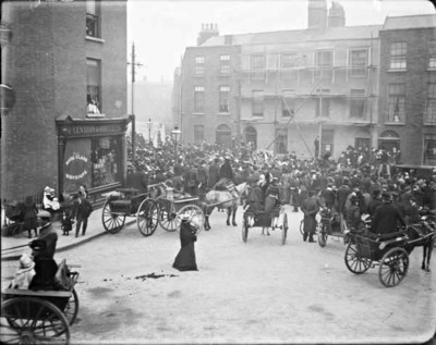 Funeral procession passing through Berkeley Street. View from Blessington Street of a crowd of mourners gathered around a horse-drawn funeral procession, as it passes through Berkeley Street. View of Lenehan & O'Neill Groceries Store at No. 26 Blessington Street/No. 19 Berkeley Street