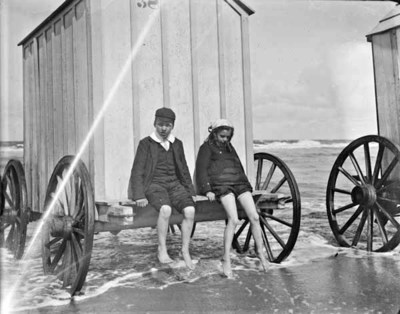 Young girl and boy sitting on a bathing box, in shallow water