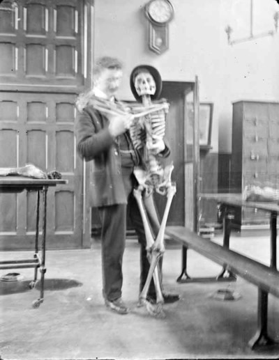 Man standing, holding skeleton to his left