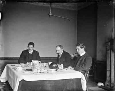 Three gentleman eating breakfast at table