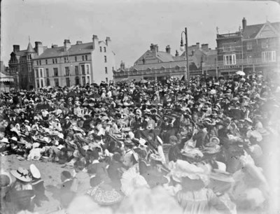 Group of spectators observing an event, possibly along a promenade. Shopfronts in the background indicate that the location of the photo may be Rhyl, Wales