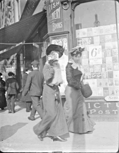 Two women walking past Sibley & Co. Stationers, No. 51 Grafton street. Woman to the left is holding a book up to cover her face