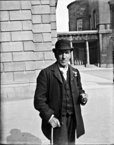 Man with cane, standing outside the National Library of Ireland and Leinster House, Kildare Street. Man wearing suit, tie and hat, holding cane in his right hand, front-facing, three-quarter length view