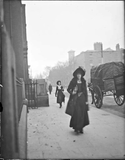 Woman walking past St. Vincent's Hospital, 55-59 St. Stephen's Green. Second woman in the background, horse and cart to the right. Italianate tower of the university building can be seen in silhouette in the background ca.1897-1904 :