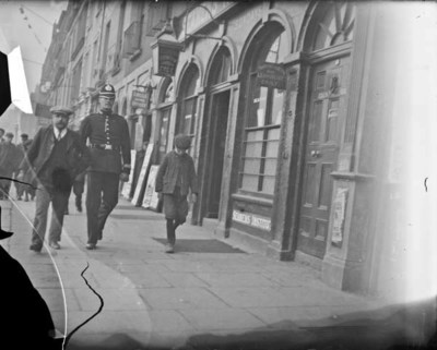 Man walking on Eden Quay accompanied by policeman. View of shop-fronts in the background including No. 12 Thomas B. O'Dell Sons Shipping and No. 13 Missions to Seamen Institute and Sailors' Reading Room