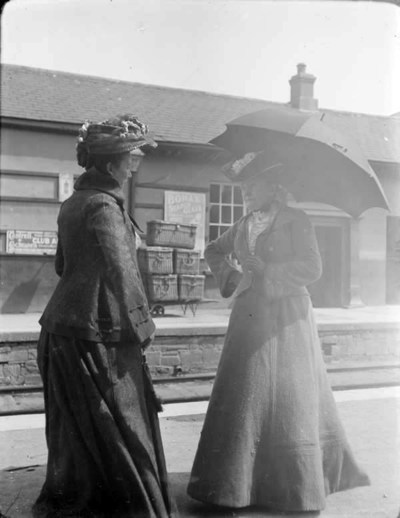 Two women standing on the platform at a train station. Two women facing each other, the one on the right holding an umbrella