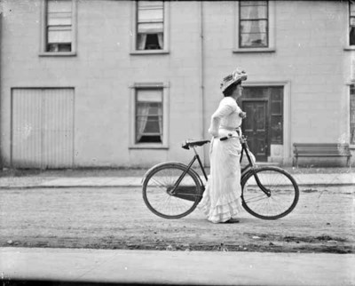 Woman with bicycle. Full-length, left-side profile of woman on bicycle