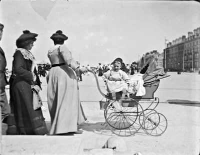 Two women and one man walking with perambulator and infant. Women pushing perambulator has face turned away from the camera, infant sitting on perambulator, man and second woman walking behind. Probably at a seaside resort