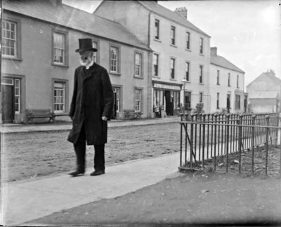 Man with beard and top hat walking along a road. Full-length view of man, probably in a rural village, shopfront and houses in background