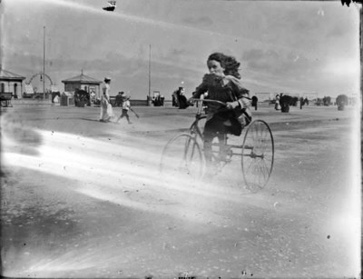 Young girl riding a tricycle along a seafront