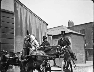 Man with driver riding a horse-drawn jaunting car. Two men are sitting to the sides of the car, back-to-back. Man to the left is probably a cab-driver, man to the right is wearing a top hat. Another horse-drawn vehicle in the background