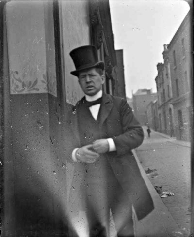 Man wearing top hat, standing in a street