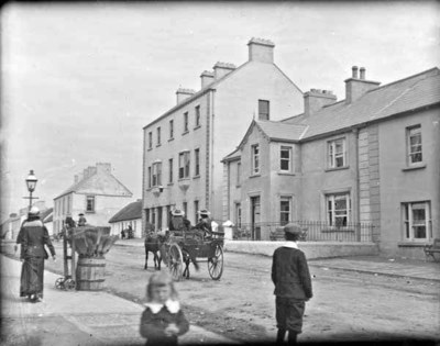 Street in a village, with horse and cart, and bystanders