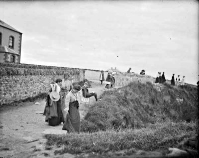 Visitors at coastal path. Groups of women, children and at least one man visiting the coast, possibly Bundoran