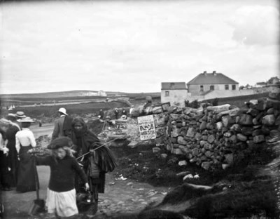 Group of people on a rural road in Bundoran. Woman and child walking in the foreground, other men and women in background, poster for James Flynn, Leather Merchant, Bundoran visible in background