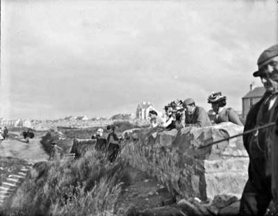 Men and women standing at a wall, probably at a coastal path. Possibly Bundoran