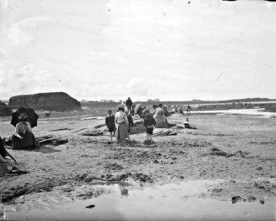 Children playing with sand at a beach, possibly Bundoran, with people in the background