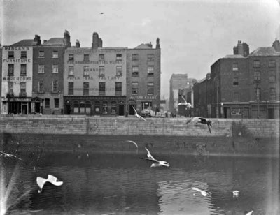 View of the River Liffey, 14-18 Ormond Quay, Lower and Swifts Row, taken from south quays. Taken from Wellington Quay, view includes Mangans Furniture Warerooms No. 14; Ormond Printing Works and Paper Bag Factory no. 16-17; James M. Forster, Picture Frame Maker, No. 18. Swift's Row also visible