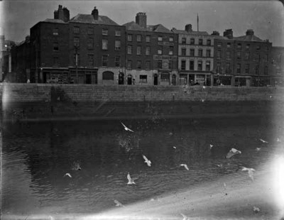 View of the River Liffey and Ormond Quay, Lower, taken from south quays. View of nos. 19-26 Ormond Quay Lower, including the Irish Card and Board Works and J.H. Hunter & Co., seed and corn merchants