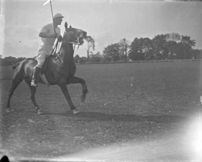 Man riding horse, holding polo stick in right hand