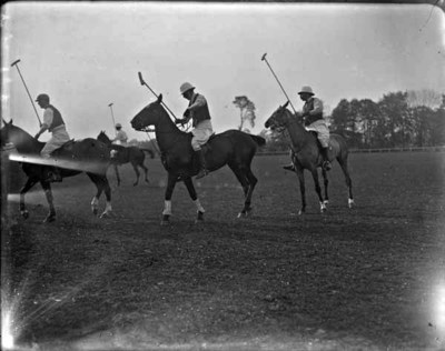 Four polo-players riding horses and holding polo-sticks.