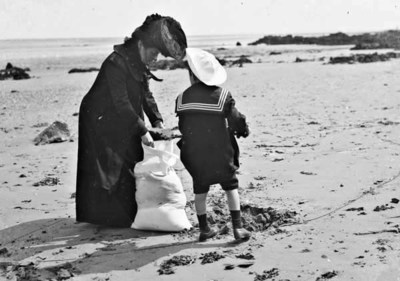 A mother and her son Trevor, filling a bag with sand on a beach, Ireland