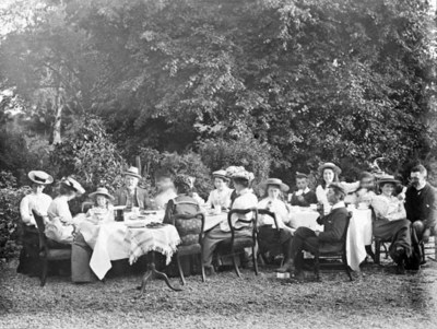 Adults and children dining at table outdoors, Ireland