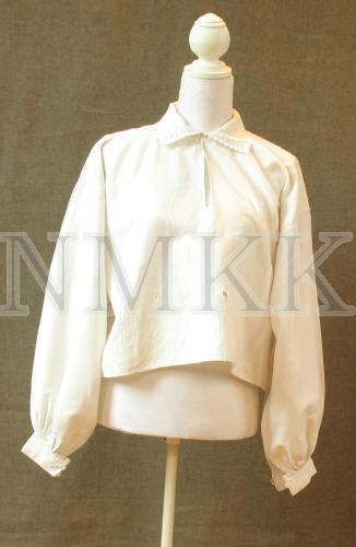 <em>Balta linu blūze tautas tērpam.Tunikveida ar taisnstūra formas uzplečiem. Plecu daļa, krādziņa un aproces rotātas ar izšuvumu baltajā tehnikā.</em>