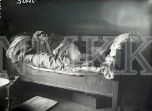 Fotonegatīvs. Veca sieviete gultā Cēsu apriņķa Rāmuļu pagasta& Pūtēju mājās.