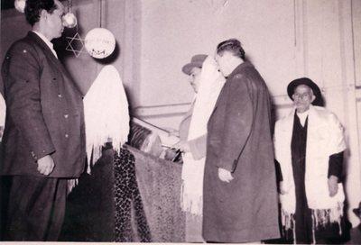 Au cours de la prière pour la santé de S. M. I. Mr. Ahmad Ghawan (?), gouverneur, et le chef de la Résistance Nationale sont debout dans une attitude recueillie. Moi-même suis revêtu du Sissit et me trouve devant le Séfer. Légende signée du directeur de l'école Ettihad Baroudjerd Ezrakian