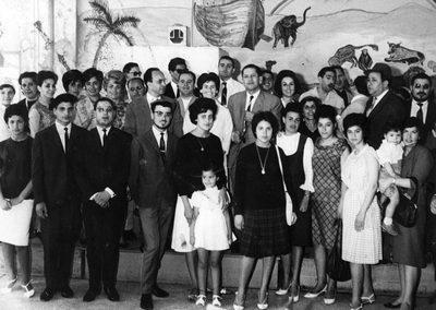 Photographie prise le 29 juin 1963 dans la salle-réfectoire de l'école de Talmud Thora, rue Zektouni (?) à Casablanca. L'ensemble des enseignants de l'Alliance langue française et des enseignants d'hébreu de la communauté, ainsi que le personnel de l'établissement (secrétaire, femmes de cuisine et de salle, coiffeur) et de la Maternelle de l'OSE (monitrices), établissement mitoyen (qui est, aujourd'hui, devenu une synagogue)