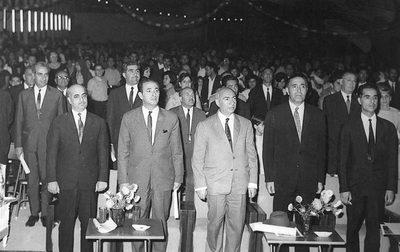 Ecoles Ettehad. Cérémonies du 25ème anniversaire du règne du Chahinchah Arya Mehr. Au 1er rang, de gauche à droite : - le colonel Taghavi, chef du 1er Bureau - M. Semsami, Directeur Général de l'I. P. - M. l'ing. Riazi, Président de la Chambre des Députés - M. l'ing. Parsa, Gouverneur Général de la 10ème Province - M. Saeb, Député d'Ispahan Au 2ème rang : - M. Farchad, Procureur Général d'Ispahan - M. Khoï, Directeur Conseil de Compagnie d'Electricité A l'extrême-droite : - M. Banel, Agent Consulaire de France à Ispahan [ou 18 mai 1965 ?]