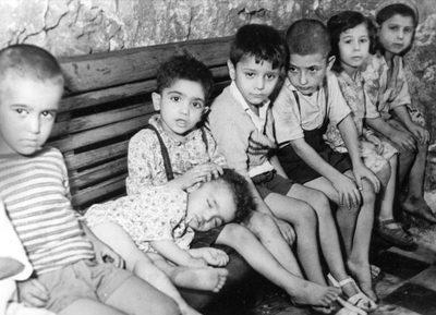 Le troisième enfant à droite a la teigne, et peut infecter sa voisine, la petite fille à gauche. Son autre voisin, le petit garçon avec les sandales blanches, est déjà infecté. [de 823 à 851 : photos du manuscrit MS 747 F : Les Hadarim de Casablanca, une étude des faits —et en images—préparée par le Bureau de l'American Joint Distribution Committee (Casablanca, septembre 1949).]