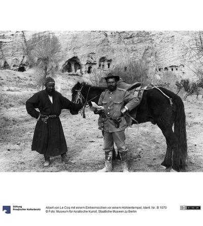 Albert von Le Coq mit einem Einheimischen vor einem Höhlentempel