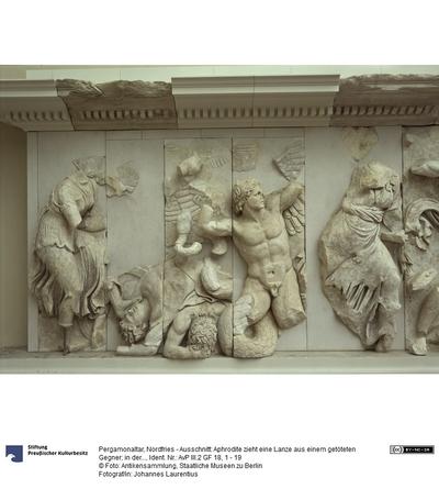 Pergamonaltar, Nordfries - Ausschnitt: Aphrodite zieht eine Lanze aus einem getöteten Gegner; in der Mitte ein geflügelter Gigant, der von Eros attakiert wird; rechts die Göttin Dione