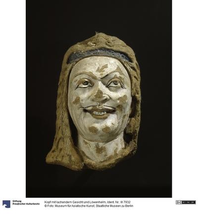 Kopf mit lachendem Gesicht und Löwenhelm