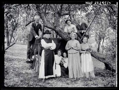 Portrait of Zubrzycki sisters with mother and few people in the orchard.