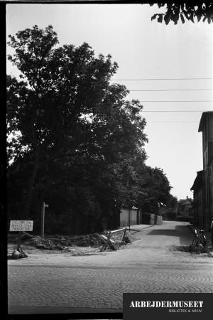 Nedrivning af et gammelt hus i Glostrup, muligvis til Vilh. Lauritzens Rådhus. Folk henvises til det modsatte fortov