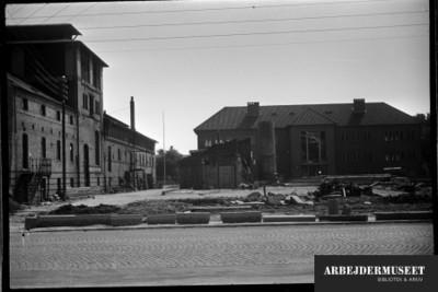 Nedrivning af et gammelt hus i Glostrup, muligvis til Vilh. Lauritzens Rådhus. teknisk skole troner i baggrunden