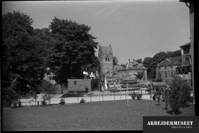 Nedrivning af et gammelt hus i Glostrup, muligvis til Vilh. Lauritzens Rådhus, kig til kirken