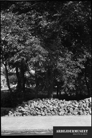 Nedrivning af et gammelt hus i Glostrup, muligvis til Vilh. Lauritzens Rådhus, bunker af sten