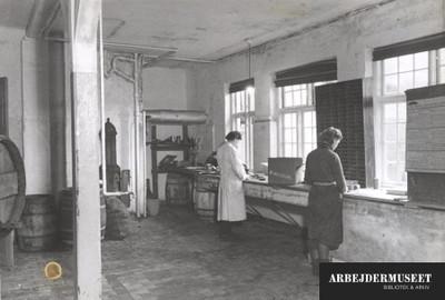 To kvinder arbejder med fiskekonserves i et rum med sildetønder