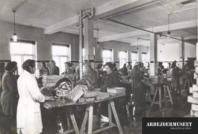 Fra produktionen hos Allert Toft fiskekonservesfabrik, kvinder står tæt ved borde og arbejder med fiskene