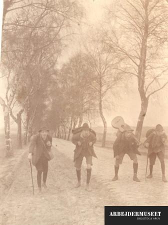 Fire friske fyre i knæbukser og strømper på vandretur med oppakning og guitar, på brostensbelagt birketræs allé